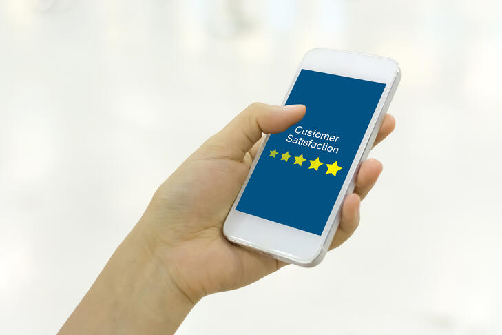 Customer-satisfaction-review-business-concept.-Woman-hand-using-smartphone-with-satisfaction-rating-online-mobile-application-1088665858_3869x2579